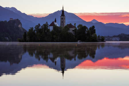 Dramatic sunrise on lake Bled, sunrise view on Bled lake, island, Pilgrimage Church of the Assumption of Maria and Castle with mountain range (Stol, Vrtaca, Begunjscica). Bled, Slovenia, Banque d'images - 142093828
