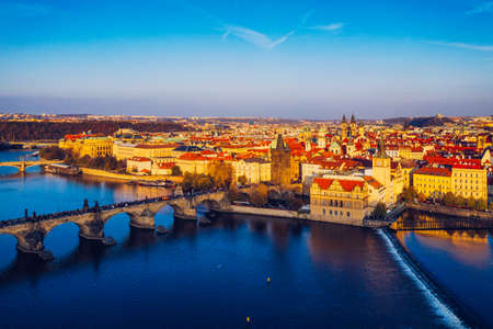 Aerial Prague panoramic drone view of the city of Prague at the Old Town Square, Czechia. Prague Old Town pier architecture and Charles Bridge over Vltava river in Prague at sunset, Czech Republic. Standard-Bild - 142093829