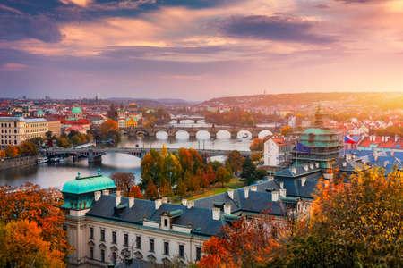 Autumn view to Charles bridge on Vltava river in Prague, Czech Republic. Autumn view to Charles Bridge, Prague old town and Vltava river. Czechia. Scenic autumn view of the Old Town with red foliage. Фото со стока - 142093890