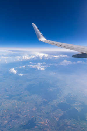 View of the wing of an airplane flying above the clouds at high altitude under a blue sky from the passenger window. In flight over Europe. View of jet airplane wing flying in blue sky over clouds. Stockfoto