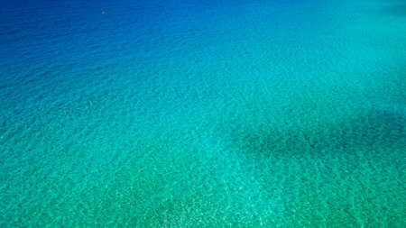 Sea surface aerial view. Background image of the turquoise sea. Deep sea and corals. Aerial drone shot of turquoise water, space for text. Aquamarine background. Sea Aerial view.