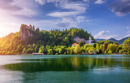 Amazing sunny scenery of Bled castle and St. Martin's Church and Bled town with reflection in the lake and the Julian Alps on background. Bled Lake, Slovenia. Stockfoto