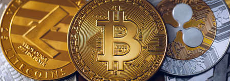 Bitcoin, litecoin and ripple coins currency finance money on graph chart background. Bitcoin as most important cryptocurrency concept. Stack of cryptocurrencies with a golden bitcoin in the middle. Stockfoto