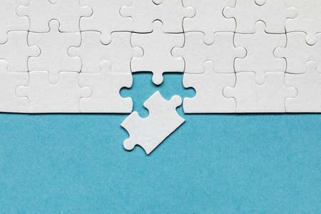 White jigsaw puzzle pieces. Fill in pieces of the jigsaw puzzle. Complete the jigsaw puzzle with the missing pieces. Fragment of a folded white jigsaw puzzle.
