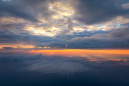 Beautiful sunset sky above clouds with dramatic light. Cabin view from airplane. Flying above the clouds. view from the airplane. Beautiful blue sky background with sunset. Sunset above the clouds.