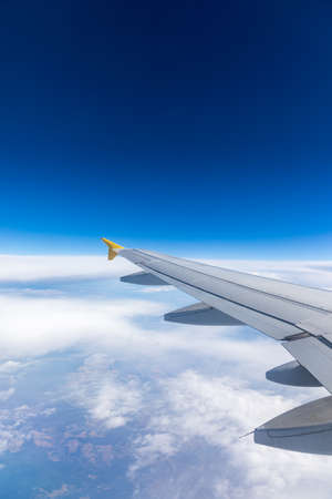 View of the wing of an airplane flying above the clouds at high altitude under a blue sky from the passenger window. In flight over Europe. View of jet airplane wing flying in blue sky over clouds. Stock fotó