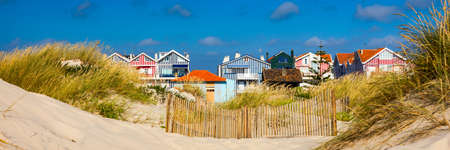 Idyllic and quaint beach houses seen from beach dunes. Beach houses with colorful stripes from Costa Nova, Aveiro, Portugal. Stock fotó
