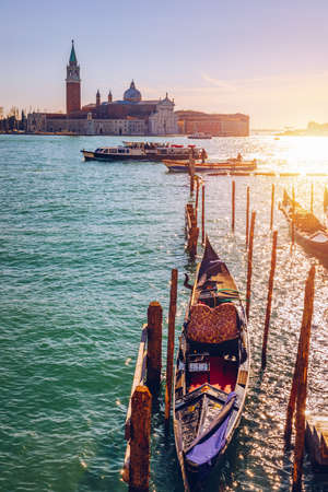 Gondolas moored near San Marco square across from San Giorgio Maggiore island in Venice, Italy. Gondolas were once the main form of transportation around the Venetian canals. Venice, Italy.