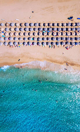Aerial view of sandy beach with colorful umbrellas, swimming people in sea bay with transparent blue water at sunset in summer. Aerial top view on the beach, umbrellas, sand and sea waves. Stockfoto - 145647991