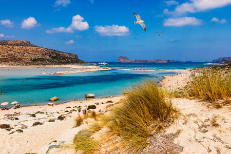 Balos Lagoon and Gramvousa island on Crete with seagulls flying over, Greece. Cap tigani in the center. Balos beach on Crete island, Greece. Crystal clear water of Balos beach. Banco de Imagens