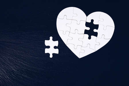 Heart-shaped jigsaw puzzle on color background. Puzzle heart on wooden background. A missing piece of the heart puzzle. Heart shape jigsaw puzzle. Puzzles in the shape of a heart. Banco de Imagens - 145649051