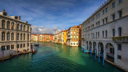Street canal in Venice, Italy. Narrow canal among old colorful brick houses in Venice, Italy. Venice postcard Stock fotó - 145649156