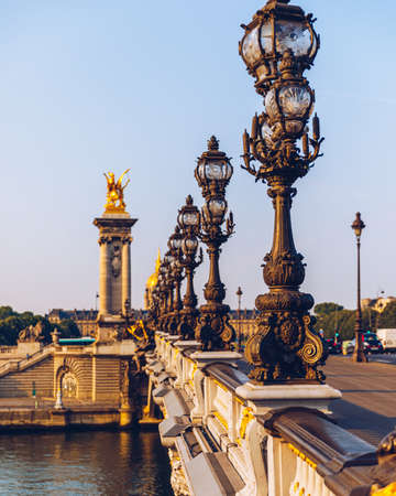 Pont Alexandre III bridge over river Seine in the sunny summer morning. Bridge decorated with ornate Art Nouveau lamps and sculptures. The Alexander III Bridge across Seine river in Paris, France. Banco de Imagens