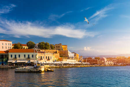 Old port of Chania with flying seagulls. Landmarks of Crete island. Bay of Chania at sunny summer day, Crete Greece. View of the old port of Chania, Crete, Greece. The port of chania, or Hania. Zdjęcie Seryjne
