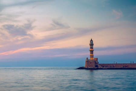 Panorama of venetian harbour waterfront and lighthouse in old harbour of Chania, Crete, Greece. Old venetian lighthouse in Chania, Greece. Lighthouse of the old Venetian port in Chania, Greece.