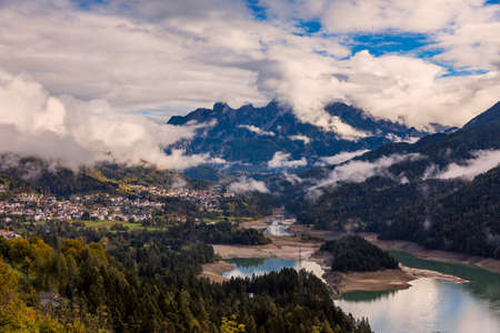 Panoramic view of lake of Centro Cadore in the Alps in Italy, Dolomites, near Belluno. View of Lake Calalzo, Belluno, Italy. Lake of Centro Cadore in the Alps in Italy, near Belluno. Archivio Fotografico - 145656977