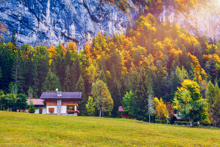 Autumn in the famous Dolomites mountains, Italy, Europe. Dramatic cliffs surround the village with the the iconic mountains and autumn forest. Colorful autumn landscape in mountain village. Zdjęcie Seryjne