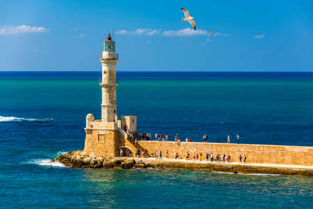 Venetian harbour and lighthouse in old harbour of Chania with seagulls flying over, Crete, Greece. Old venetian lighthouse in Chania, Greece. Lighthouse of the old Venetian port in Chania, Greece. Banque d'images - 145657184