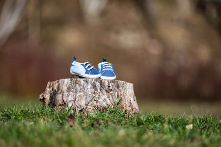 Young couple waiting for baby. Expecting parents with little baby boy shoes. Concept of Parents-To-Be. Shoes and sneakers of parents and expected baby. Mom, dad and the future baby Shoes. Banco de Imagens - 155850264