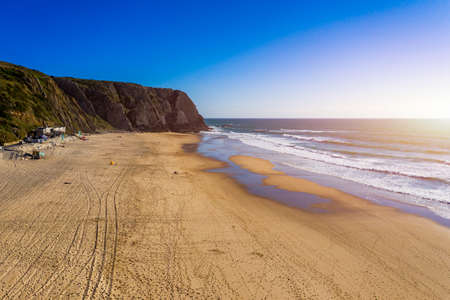 Praia Grande, Portugal. Beautiful sunset in the portuguese beach Praia Grande, in Portugal. Beach of Praia Grande. View of Atlantic beach and big waves. Colares, Sintra, Portugal. Stok Fotoğraf - 154897806