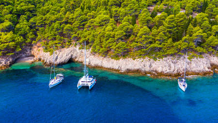 Yacht anchoring in crystal clear turquoise water in front of the tropical island, alternative lifestyle, living on a boat. Aerial view of yacht at anchor on turquoise water, showing luxury, wealth. 写真素材 - 155850276