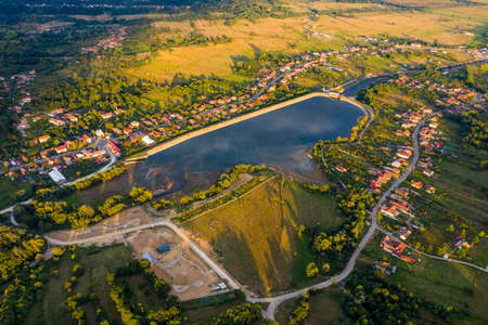 Beautiful Tismana lake and surrounding forest aerial panorama. Tismana, Romania.