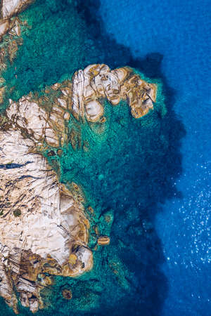Aerial photo over granite rocky coastline Mediterranean crystal clear blue sea water. Aerial photo of ocean waves hitting rocky coastline of beautiful paradise dream tropical beach. Sardinia, Italy. Фото со стока