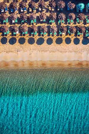 View from above, stunning aerial view of an amazing beach with beach umbrellas and turquoise clear water. Top view on sun loungers under umbrellas on the sandy beach. Concept of summer vacation.