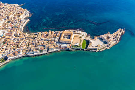 Siracusa, Ortigia Island from the air, Sicily, Italy. Isola di Ortigia, coast of Ortigia island at city of Syracuse, Sicily, Italy. Coastline town Syracuse, Sicily and old Ortigia island. Aerial view. Stok Fotoğraf