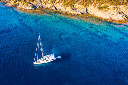 Aerial view of anchored sailing yacht in emerald sea. Aerial view of a boat. Outdoor water sports, yachting. Aerial view of anchoring yacht in open water. Ocean and sea travel and transportation Stockfoto - 154889401