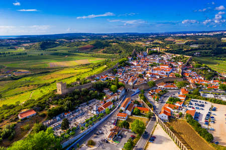 Aerial view of the historic walled town of Obidos at sunset, near Lisbon, Portugal. Aerial shot of Obidos Medieval Town, Portugal. Aerial view of medieval fortress in Obidos. Portugal.