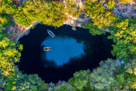 Melissani lake on Kefalonia island, Greece. Melissani Cave (Melissani Lake) near Sami village in Kefalonia island, Greece. Tourist boat on the lake in Melissani Cave, Kefalonia Island, Greece