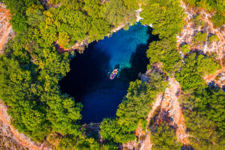 Melissani lake on Kefalonia island, Greece. Melissani Cave (Melissani Lake) near Sami village in Kefalonia island, Greece. Tourist boat on the lake in Melissani Cave, Kefalonia Island, Greece Stok Fotoğraf - 154888594