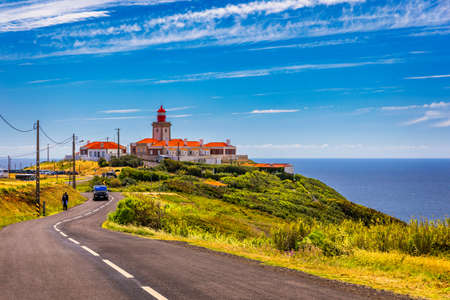 The lighthouse in Cabo da Roca. Cliffs and rocks on the Atlantic ocean coast in Sintra in a beautiful summer day, Portugal. Cabo da Roca, Portugal. Lighthouse and cliffs over Atlantic Ocean. Фото со стока - 154888485