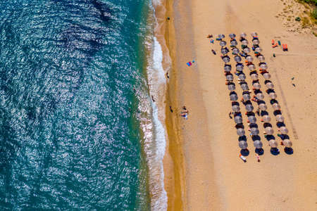 View from above, stunning aerial view of an amazing beach with beach umbrellas and turquoise clear water. Top view on sun loungers under umbrellas on the sandy beach. Concept of summer vacation. Stok Fotoğraf - 154888212