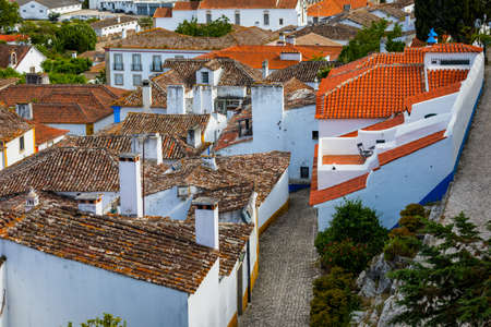 Historic walled town of Obidos, near Lisbon, Portugal. Beautiful streets of Obidos Medieval Town, Portugal. Street view of medieval fortress in Obidos. Portugal. Stok Fotoğraf - 154888226