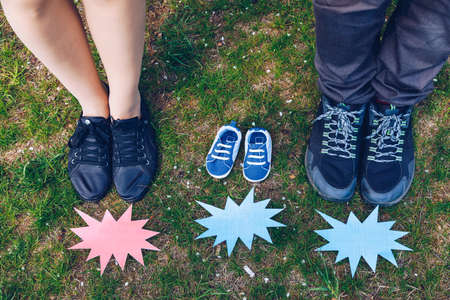 Young couple waiting for baby. Expecting parents with little baby boy shoes. Concept of Parents-To-Be. Shoes and sneakers of parents and expected baby. Mom, dad and the future baby Shoes.