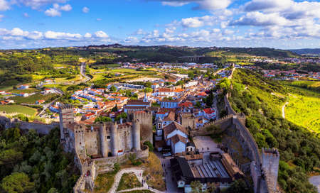 Aerial view of the historic walled town of Obidos at sunset, near Lisbon, Portugal. Aerial shot of Obidos Medieval Town, Portugal. Aerial view of medieval fortress in Obidos. Portugal. Banco de Imagens - 156156135