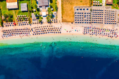 Concept of summer vacation. View from above, stunning aerial view of an amazing beach with beach umbrellas and turquoise clear water. Top view on a sun lounger under an umbrella on the sandy beach