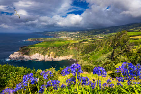 View from Miradouro de Santa Iria on the island of São Miguel in the Azores. The view shows part of the northern coastline with cliffs and green fields on the clifftop. Azores, Sao Miguel, Portugal Stok Fotoğraf