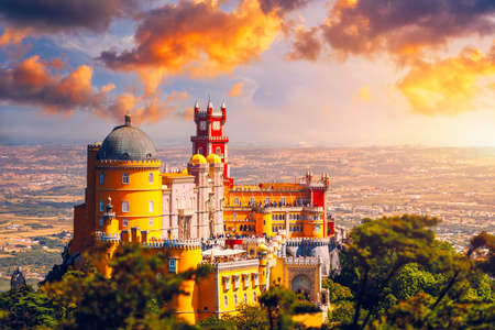 Famous historic Pena palace part of cultural site of Sintra against sunset sky in Portugal. Panoramic View Of Pena Palace, Sintra, Portugal. Pena National Palace at sunset, Sintra, Portugal. 写真素材 - 154912101
