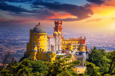 Famous historic Pena palace part of cultural site of Sintra against sunset sky in Portugal. Panoramic View Of Pena Palace, Sintra, Portugal. Pena National Palace at sunset, Sintra, Portugal. Archivio Fotografico - 154912102
