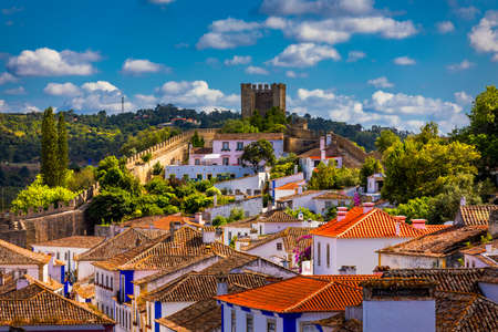 Historic walled town of Obidos, near Lisbon, Portugal. Beautiful streets of Obidos Medieval Town, Portugal. Street view of medieval fortress in Obidos. Portugal. Zdjęcie Seryjne - 156134162