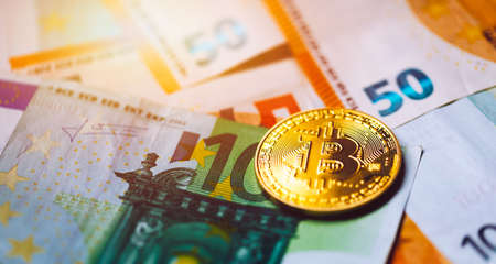 Bitcoin cryptocurrency (crypto currency) over Euro money. Golden Bitcoin symbol. Bitcoin (BTC) cryptocurrency.