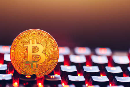 Bitcoin on compuer keyboard in background, symbol of electronic virtual money and mining cryptocurrency concept. Coin crypto currency bitcoin lies on the keyboard. Bitcoin on keyboard.