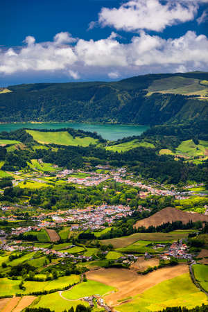 View of Furnas town and lake (Lagoa das Furnas) on Sao Miguel Island, Azores, Portugal from the Miradouro do Salto do Cavalo viewpoint. A tranquil scene of lush foliage and town in a volcanic crater
