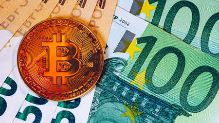 Golden bitcoin over Euro money. Bitcoin cryptocurrency. Crypto currency concept. Bitcoin with euro bills. Bitcoins stacked on euro banknotes.