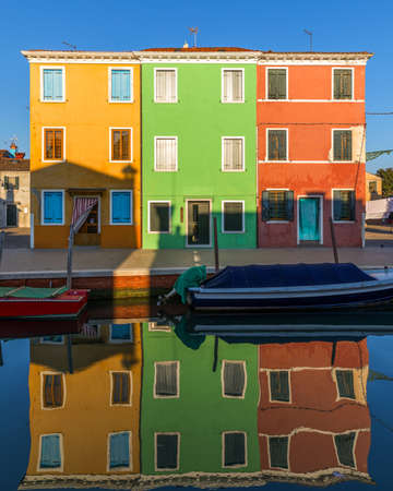 Street with colorful buildings in Burano island, Venice, Italy. Architecture and landmarks of Burano, Venice postcard. Scenic canal and colorful architecture in Burano island near Venice, Italy Фото со стока