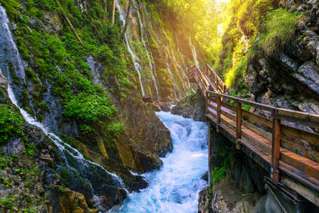 Beautiful Wimbachklamm gorge with wooden path in autumn colors, Ramsau bei Berchtesgaden in Germany. Waterfall at Wimbachklamm near Ramsau-Berchtesgaden, Bavaria, Germany.
