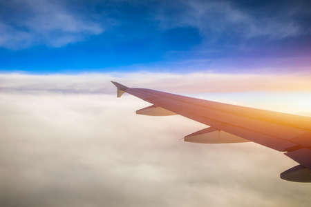 Flying and traveling, view from airplane window on the wing on sunset time. Aircraft wing under the earth and clouds. Flight in sky. Looking over aircraft wing in flight. Archivio Fotografico